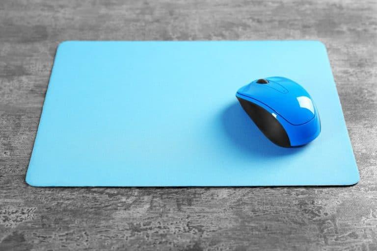 Imagem de mouse pad azul sobre mesa com mouse em cima.