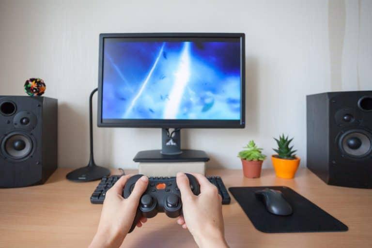 Imagem de mãos segurando controle em frente a um computador.