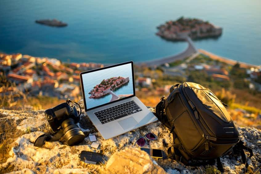 Notebook, câmera e mochila em montanha com mar ao fundo.