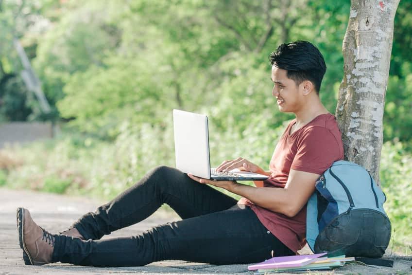 Homem em parque com notebook e bolsa ao lado.
