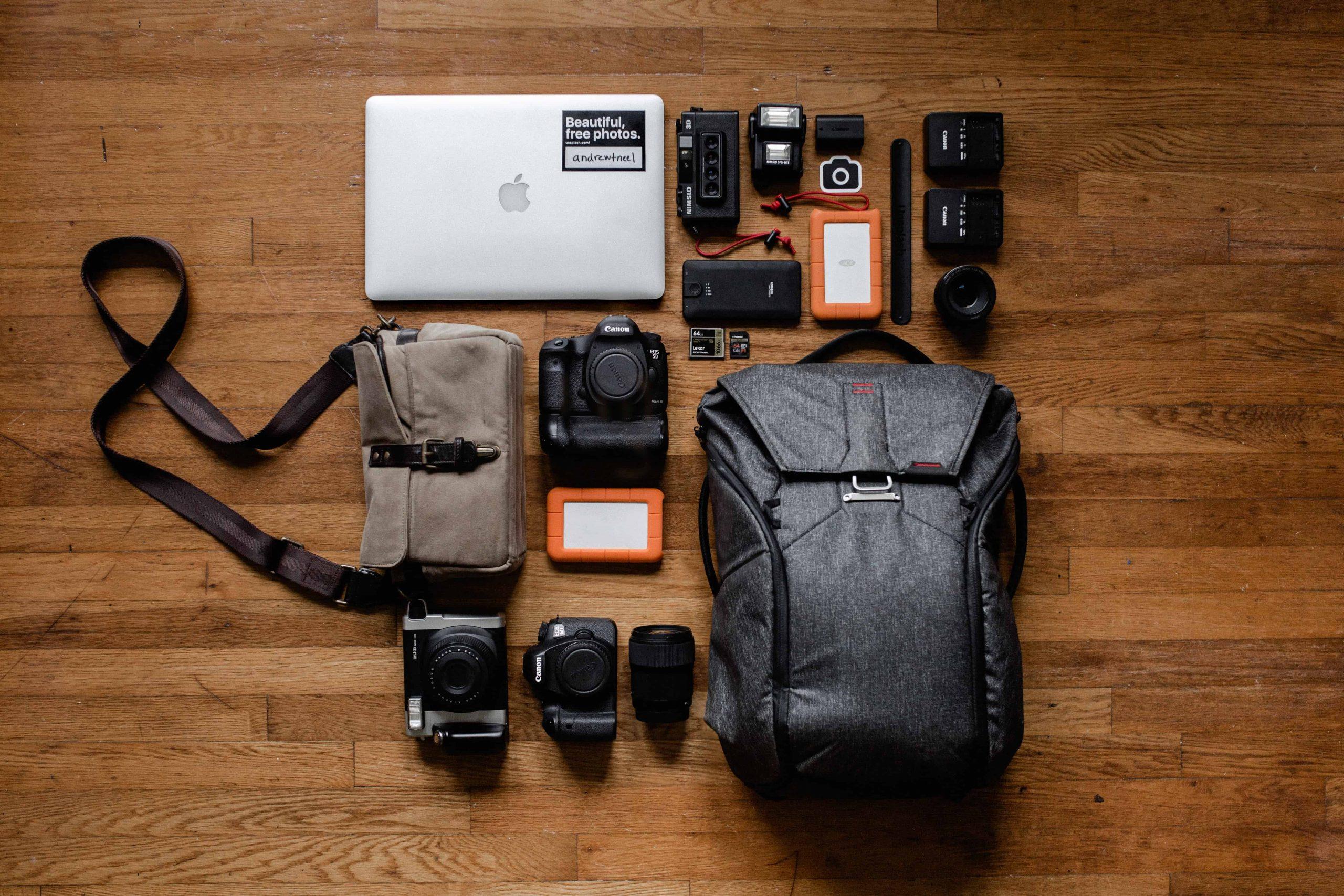Câmera, notebook e outros equipamentos sobre mesa.