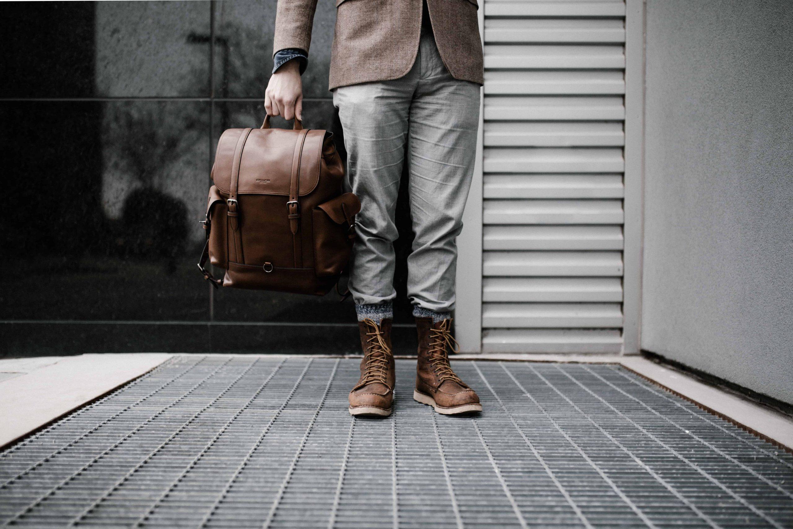 Imagem de homem em pé segurando bolsa marrom.
