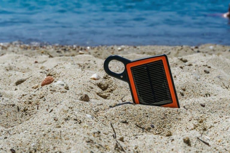 Um carregador solar na areia da praia.