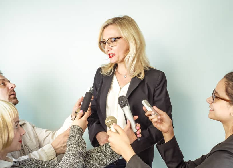 Jornalistas entrevistando uma mulher.