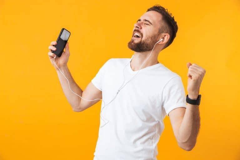 Homem feliz ouvindo música com fones.