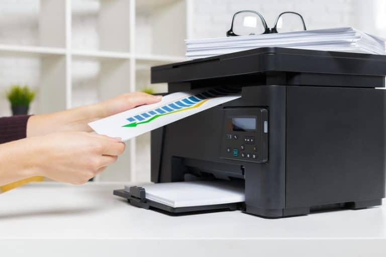 Imagem de pessoa imprimindo documento em impressora multifuncional.