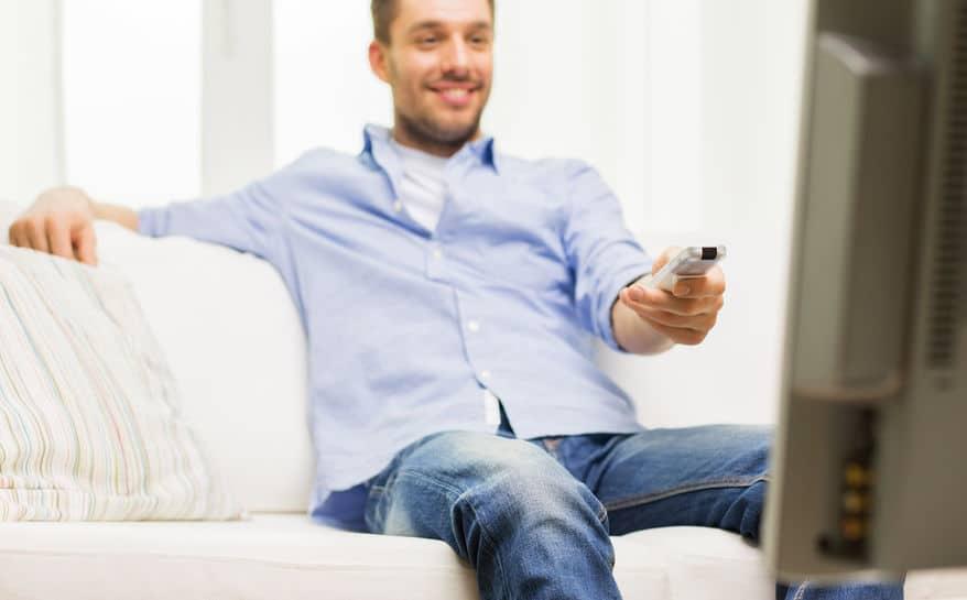 Homem com controle remoto assistindo TV.