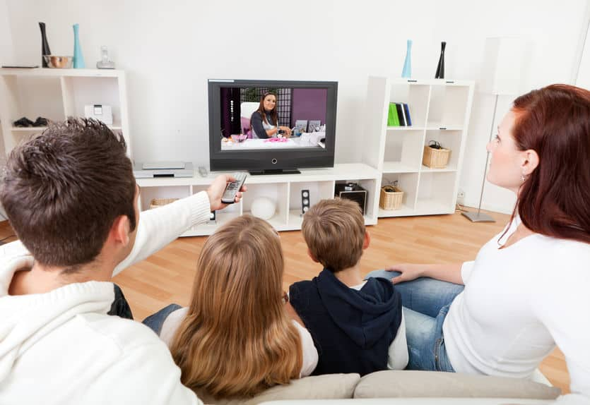 Família no sofá assistindo TV.