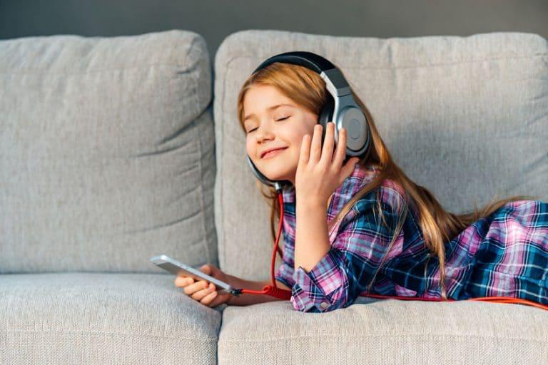 Menina em sofá escutando música com fone de ouvido Sony.