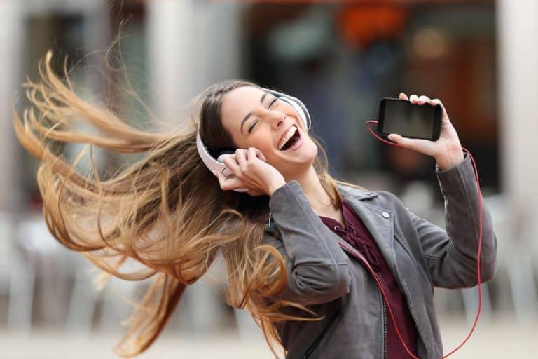 Mulher feliz ouvindo música.
