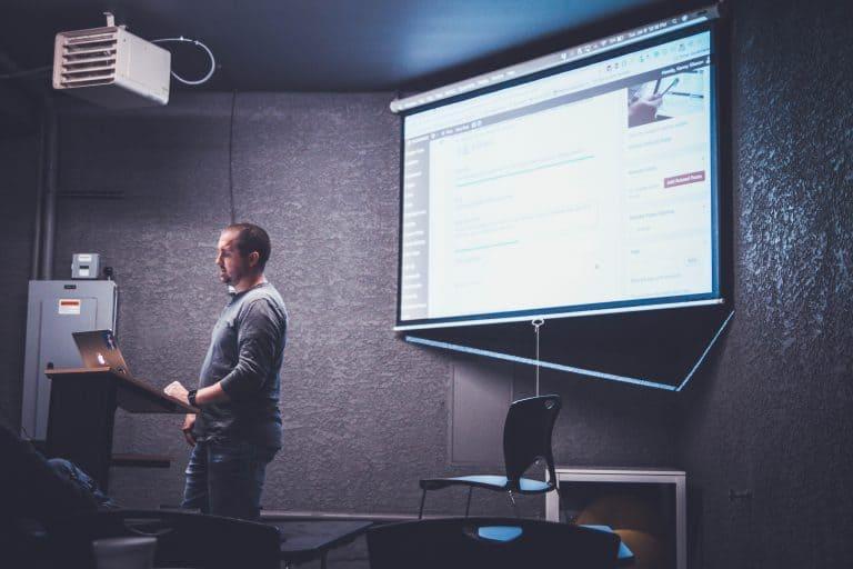 Imagem de homem realizando palestra.