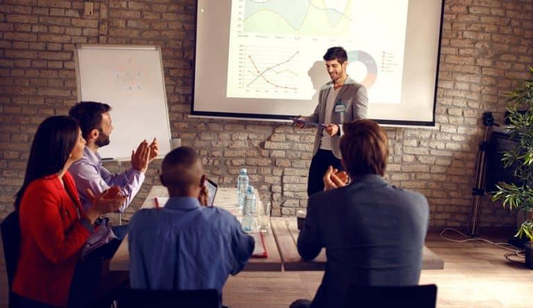 Imagem de pessoas em reunião com projeção.