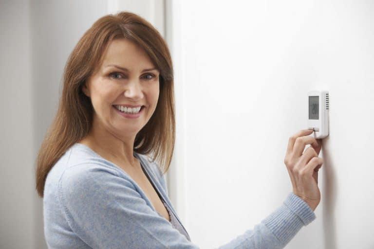 Imagem de mulher ligando termostato.